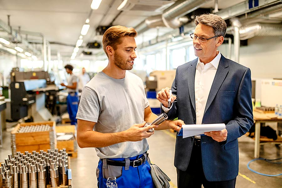 Interner Unternehmensverkauf: Unternehmer und Führungskraft im Gespräch in einer Fabrikhalle.