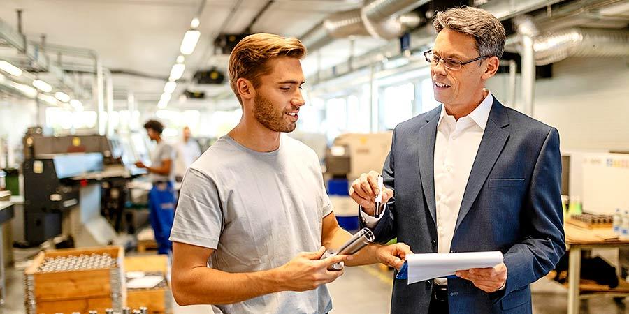 Interner Unternehmensverkauf: Auf was dabei zu achten ist. Gespräch zwischen zwei Männern in einer Fabrikhalle.